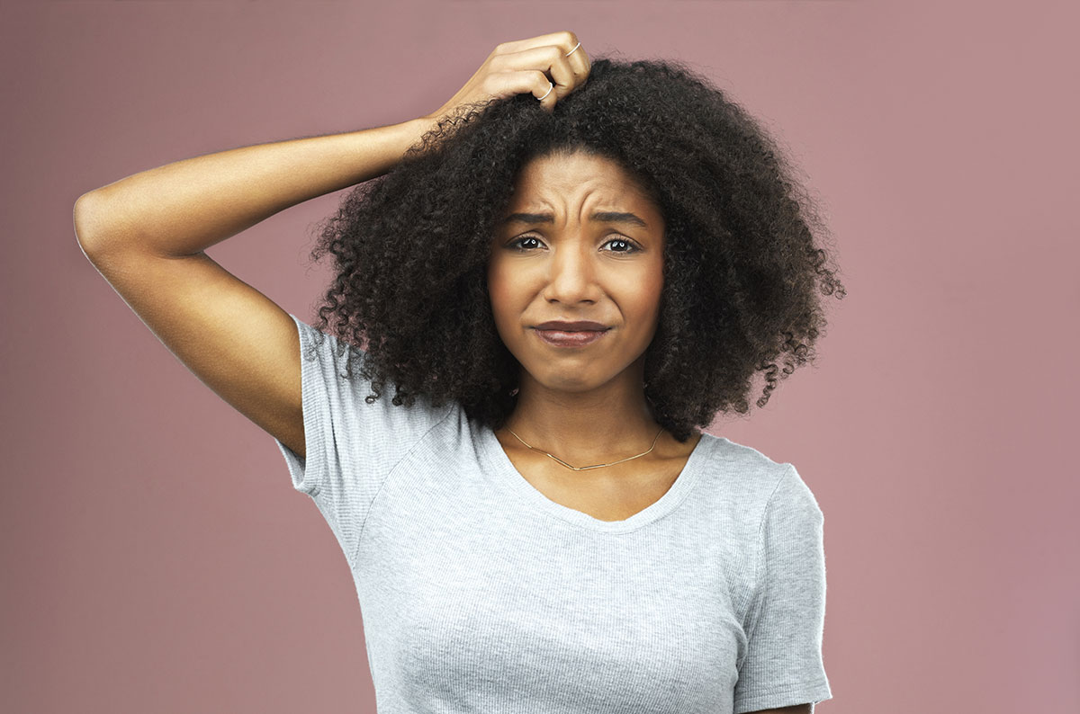 Woman with long afro hair looking concerned